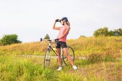Porträt eines jungen weiblichen Sportathleten mit laufendem Fahrrad restin Lizenzfreies Stockfoto