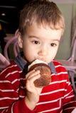 Porträt eines kleinen Jungen, der geschmackvolles Kakaomuffin mit gepeitschtem Belag isst Stockbilder