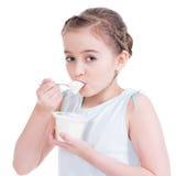 Porträt eines kleinen Mädchens, das Jogurt isst. Lizenzfreies Stockbild