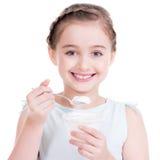 Porträt eines kleinen Mädchens, das Jogurt isst. Stockbilder