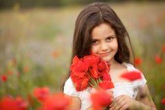 Porträt eines kleinen Mädchens mit Mohnblumen Stockbild