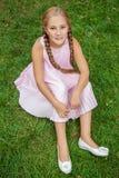 Porträt eines lächelnden kleinen Mädchens, das auf grünem Gras mit der toothy Lächeln- und Zopffrisur betrachten Kamera und glück Stockfotografie