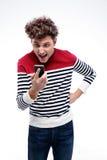 Porträt eines Mannes, der am Smartphone schreit Stockbilder