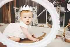 Porträt eines netten Babys mit Papierkrone Stockbild