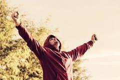 Porträt eines netten jungen Mannes mit der Armverbreitung offen draußen Stockfotografie