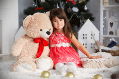 Porträt eines netten kleinen Brunettemädchens, das einen großen Teddybären umarmt Stockbild