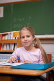 Porträt eines netten Schulmädchenschreibens Stockbild