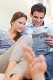 Porträt eines Paares, das eine Zeitung beim Lügen auf einer Couch liest Lizenzfreie Stockfotografie