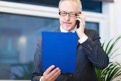 Porträt eines reifen Geschäftsmannes, der am Telefon spricht Stockbilder