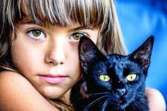 Porträt eines schönen kleinen Mädchens, das eine schwarze Katze hält Lizenzfreie Stockfotos
