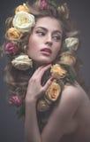 Porträt eines schönen Mädchens mit einem leichten rosa Make-up und vielen Blumen in ihrem Haar Eine Wiese mit blühenden Apfelbäum Lizenzfreies Stockfoto