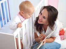 Porträt eines schönen Mutterlesebuches zum netten Baby Stockfotos