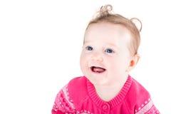 Porträt eines süßen Babys mit dem gelockten Haar und blauen den Augen, die eine rosa Strickjacke mit Herzmuster tragen Stockbilder