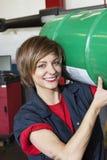 Porträt eines tragenden Ölfasses des glücklichen Mechanikers in der FahrzeugReparaturwerkstatt Lizenzfreies Stockbild