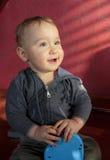 Porträt eines zwei-Jahr-alten Jungen, der auf dem Boden und dem Lächeln sitzt Stockfotografie
