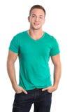 Porträt: Glücklicher lokalisierter junger Mann, der grünes Hemd und Jeans trägt Stockbild
