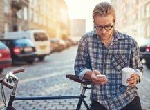 Porträt im Freien des modernen jungen Mannes mit Handy Stockfotografie