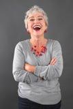 Porträt lächelnder älterer Dame im Grau Stockbild