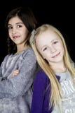 Porträt mit zwei jungen Mädchen, welches die Kamera entzückend betrachtet Stockfotografie