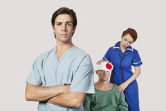 Porträt männlichen Doktors mit der weiblichen Krankenschwester, die einen verletzten Patienten gegen grauen Hintergrund behandelt Lizenzfreie Stockbilder