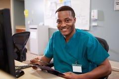 Porträt männlicher Krankenschwester-Working At Nurses-Station Stockbild