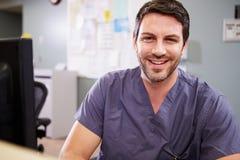 Porträt männlicher Krankenschwester-Working At Nurses-Station Lizenzfreies Stockfoto