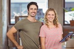 Porträt von den frohen Geschäftsleuten, die im Büro stehen Stockbilder