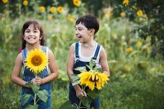 Porträt von den netten Mädchen, die hinter Sonnenblumen sich verstecken Lizenzfreies Stockbild