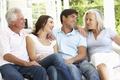 Porträt von den reifen Eltern, die mit herangewachsenen Kindern sich entspannen Lizenzfreies Stockfoto