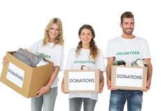 Porträt von drei lächelnden jungen Leuten mit Spendenkästen Lizenzfreie Stockfotos