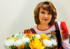 Porträt von fünfzig gut-pflegte Frau im russischen Volkskostüm mit einem Blumenstrauß von Blumen Lizenzfreies Stockfoto