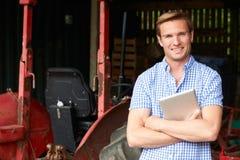 Porträt von Landwirt-With Old Fashioned-Traktor und von Digital-Tablet Stockfotografie