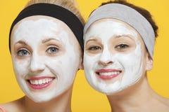 Porträt von zwei glücklichen Frauen mit Gesichtsmaske auf ihren Gesichtern über gelbem Hintergrund Stockfoto