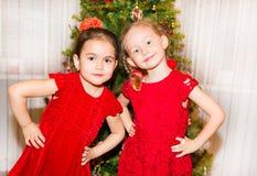 Porträt von zwei Kindermädchen um einen Weihnachtsbaum verziert Kind auf neuem Jahr des Feiertags Stockfoto