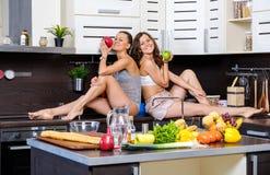 Porträt von zwei Zwillingsschwestern, die den Spaß morgens zubereitet Frühstück haben Lizenzfreie Stockbilder