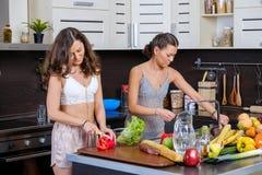 Porträt von zwei Zwillingsschwestern, die den Spaß morgens zubereitet Frühstück haben Stockfotografie