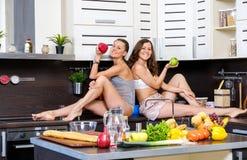 Porträt von zwei Zwillingsschwestern, die den Spaß morgens zubereitet Frühstück haben Lizenzfreie Stockfotos