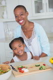Porträtmutter und -tochter, die zusammen einen Salat machen Stockfoto