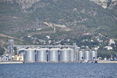 Portside Plant For Storage, Drying And Handling Of Grain. Port Freight Infrastructure. Cargo Port With Port Cranes. Sea Bay And Mo Stock Photos