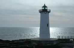 Portsmouth Harbor Lighthouse. Against a background of clouds with sun shining a path on the ocean stock photo