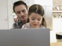 Portátil de And Daughter Using do pai em casa Imagens de Stock