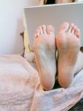 Portátil e pés Imagens de Stock Royalty Free