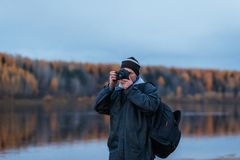 Porttrait of amateur photographer shooting the autumn scenery of the river. Landscape therapy. Portrair of amateur photographer shooting the autumn scenery of royalty free stock photo