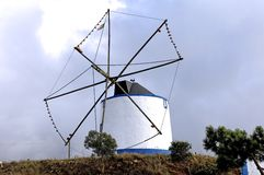 Portugal, Alentejo: Wind mill. Portugal, Alentejo: blue and cloudy sky and a small white wind mill on the top of a hill royalty free stock images