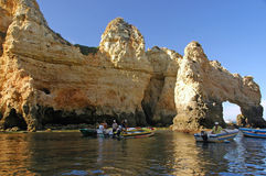 Portugal, Algarve. Fishermen in their work. In the background the typical rock formation in the Algarve Stock Photos