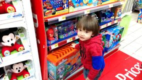 Little boy choosing toys. Portugal, Algarve, Circa March 2018. Little 3 year old boy looking at toys in a Jumbo supermarket Stock Images