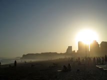 Portugal, Algarve, Portimao, Praia da Rocha. Beach with people and town in sunset time, horizontal view. Royalty Free Stock Photos