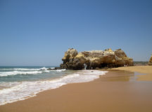 Portugal, Algarve, Portimao, Praia da Rocha. Wave of atlantic ocean, sand and rock on blue sky background, horizontal view. Royalty Free Stock Photos