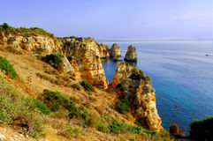 Portugal, area of Algarve, Lagos: rocky coastline. Portugal, area of Algarve, Lagos: yellow rocky coastline with blue sky and blue ocean royalty free stock images