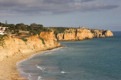 Portugal Coastline. The cliffs and coastline of Portugal, with the town of Lagos in the distance Royalty Free Stock Image